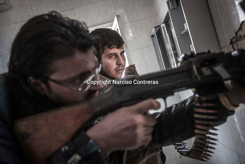 In this Sunday, Oct. 28, 2012 photo. Rebel fighters belonging to the Liwa Al-Tawhid keep an eye over the enemy position as they prepare themselves to open fire while mortar explosions and gun machine shoots sound at the battlefield in Karmal Jabl neighborhood in Aleppo, the Syrian's largest city. (AP Photo/Narciso Contreras).
