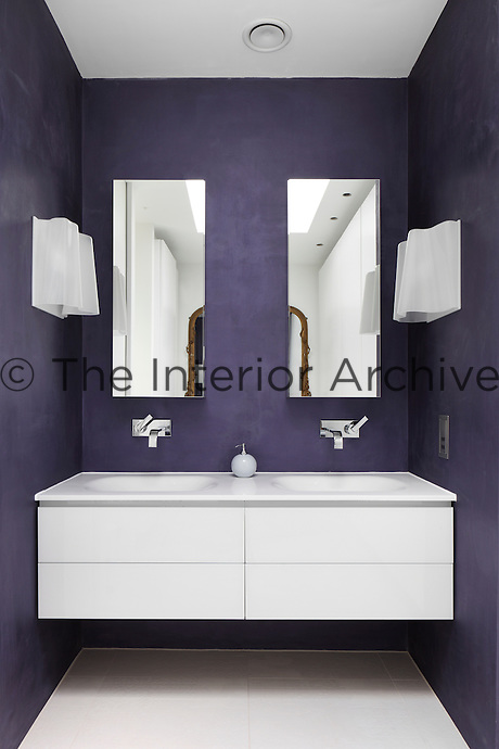 Two wash basins above a wall-mounted drawer unit set in a purple recess.