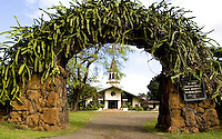 Ferns grow on a lava rock arch in front of a church in Haleiwa on the North Shore of Oahu.