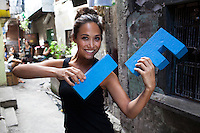 Myleene Klass, a high profile UK celebrity, TV host, violinist and pianist, uses the IF letters as a violin for the IF campaign, photographed in Paranaque, Metro Manila, The Philippines. Photo by Suzanne Lee for Save the Children UK