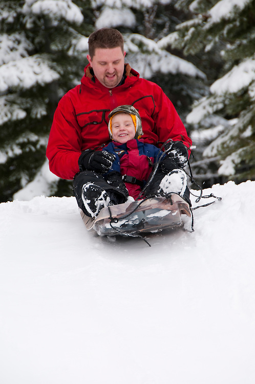 California, Lake Tahoe: Child and father enjoy snow play with sled at North Lake Tahoe Regional Park.  Photo copyright Lee Foster.  Photo # cataho107516