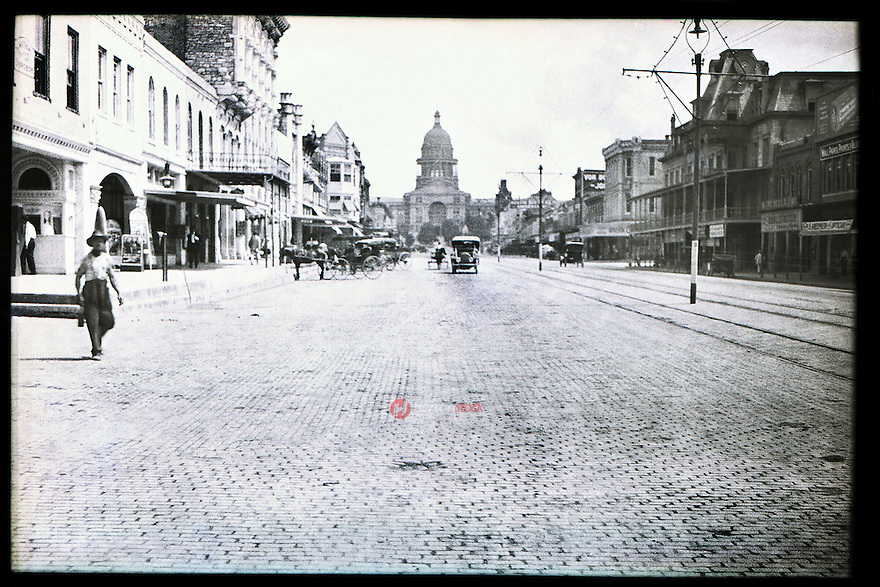 In the picture you can see Congress Avenue as it appeared in 1913, looking toward the capitol building. Antique cars and horse drawn carriages going up and down Congress Avenue cobblestone streets next to the cable car tracks leading up the Texas State Capitol.