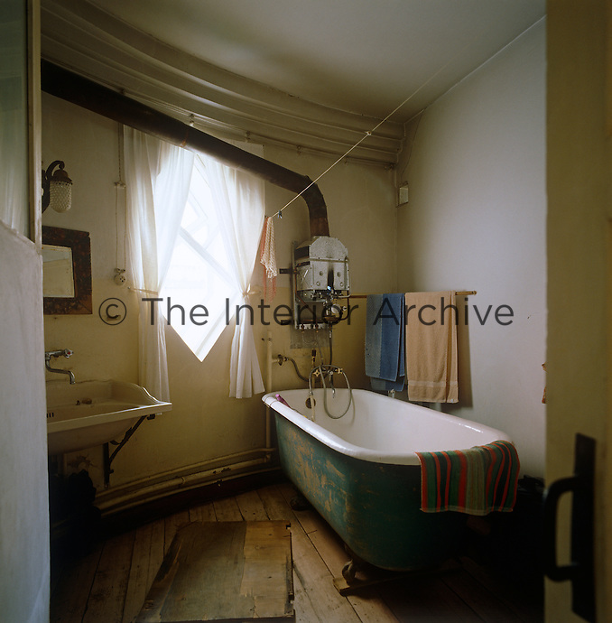 The shabbily evocative bathroom with its scrubbed floor and ancient geyser