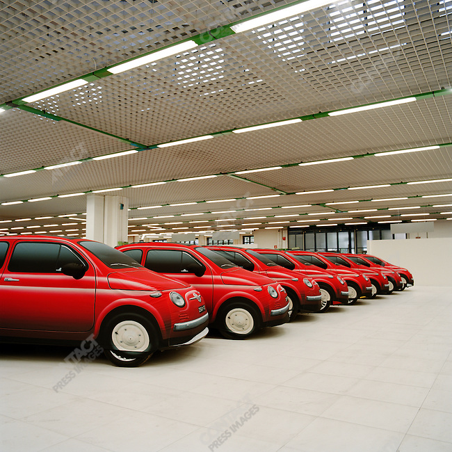 At the FIAT Centre in Rome new Cinquecento model cars, which have been selling fast since their introduction, stood parked in a line, protected by identical covers. October 25, 2007