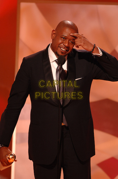 "FOREST WHITAKER.Accepts the award for Best Performance By An Actor In A Motion Picture Drama for ""The Last King of Scotland"".Telecast - 64th Annual Golden Globe Awards, Beverly Hills HIlton, Beverly Hills, California, USA..January 15th 2007.globes half length microphone black suit jacket trophy.CAP/AW.Please use accompanying story.Supplied by Capital Pictures.© HFPA"" and ""64th Golden Globe Awards"""