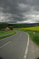 Cloudy sky over country road with yellow oilseed rape in fields. Aschaffenburg district, Germany.