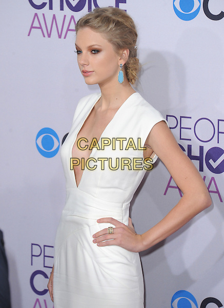 Taylor Swift.The 2013 People's Choice Awards held at Nokia Live in Los Angeles, California 9th January 2013                                                                   .half length white dress plunging neckline  cleavage hand on hip blue turquoise earrings profile .CAP/DVS.©DVS/Capital Pictures.