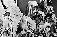 Gul Payenda Mohammad with one of her children in the ruins of a house in Aqrabat, Aghanistan on Thursday, June 27, 2002. Her husband was killed when the family had to flee the Taliban attack on her home village of Saighan in 2001. 46 ethnic Hazara widows and their children live in Aqrabat. More than six million people fled Afghanistan during the years of conflict following the Soviet invasion in 1979.
