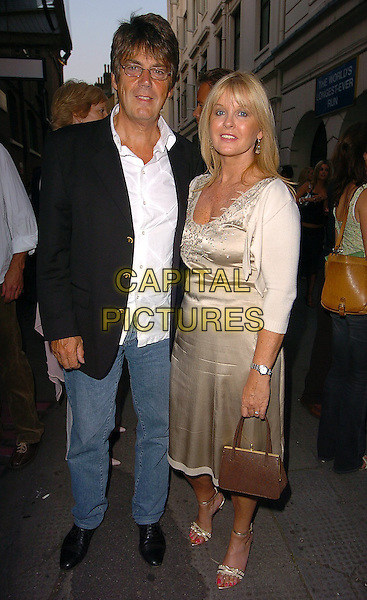 "MIKE READ & PARTNER.""Telstar"" Gala performance,.Ambassador Theatre,.London, 17th August 200.full length black navy suit jacket denim jeans white shirt satin dress cream shrug cardigan strappy sandals shoes brown handbag glasses eye contact.www.capitalpictures.com.sales@capitalpictures.com.©Capital Pictures"