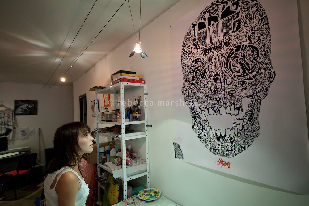 A gallery visitor looks at a poster designed by Thomas Auvin at 'En Traits Libres' gallery and workshop, Montpellier, France, 14 July 2012. 'En Traits Libres' is a collective of 11 local artists, animators and comic book illustrators.