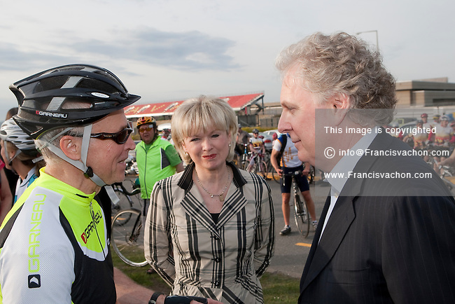 Universite Laval teacher Jean-Marie De Koninck and Quebec Premier Jean Charest as Quebec Minister of Transport Julie Boulet  looks on before the Ride in Silence event in Quebec City May 19, 2010. Ride in Silence is a worldwide event being held tonight to honor those injured or killed while cycling on public roads.