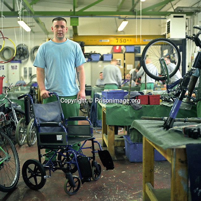 An inmate working to recondition an old wheel chair in the Inside Out trust workshop. HMP Liverpool, Merseyside, United Kingdom. Inmates at HMP Liverpool will work during the day in industrial workshops, or doing laundry and other such tasks.