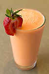 An orange smoothie with a strawberry garnish