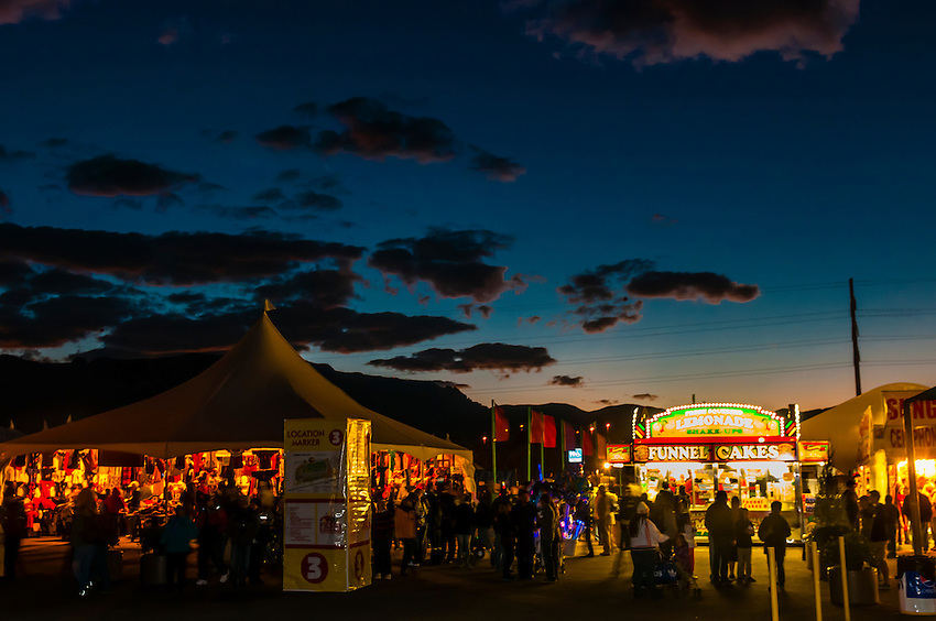 People walking along the midway (shopping and food) at the Albuquerque International Balloon Fiesta before sunrise, Albuquerque, New Mexico USA.