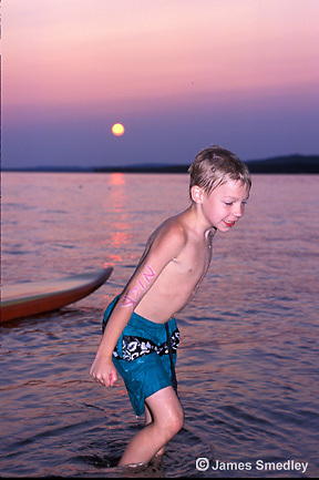 Young boy swimming in the lake at sunset