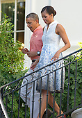 United States President Barack Obama and first lady Michelle Obama walk down the South Portico stairs to work the rope line as they host a Fourth of July barbecue for military heroes and their families on the South Lawn of the White House in Washington, D.C. on Thursday, July 4, 2013.<br /> Credit: Ron Sachs / Pool via CNP