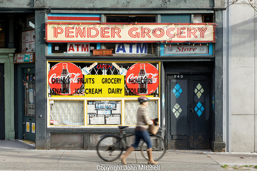 Woman with bicycle walking past a grocery store on Pender Street, Vancouver Downtown Eastside, Vancouver, BC, Canada