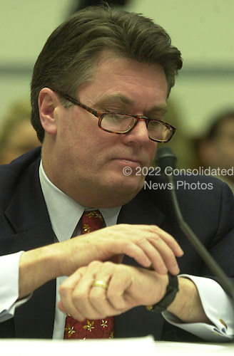 Jack Quinn, former White House counsel and attorney for Marc Rich, checks his watch as he testifies before the United States House Committee on Government Reform and Oversight in Washington, D.C. on 8 February, 2001..Credit: Ron Sachs / CNP