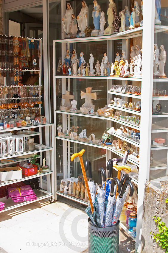 A shop with souvenirs for pilgrims, with things for sale. Madonna statue, rosary beads, post cards, umbrellas... Medugorje pilgrimage village, near Mostar. Medjugorje. Federation Bosne i Hercegovine. Bosnia Herzegovina, Europe.