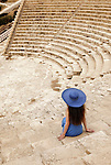 Elegant young woman sitting alone at empty ancient Greco-Roman amphitheatre. Kourion, Cyprus.