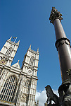 West front face of Westminster Abbey and nearby memorial column against blue sky