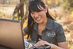 Cheetah (Acinonyx jubatus) biologist, Kim Young-Overton, looking at camera trap images, Kafue National Park, Zambia