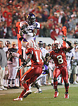 25 November 2006: East Carolina's Aundrae Allison (2) leaps over NC State's J.C. Neal (14) and Jimmie Sutton III (8) and catches a pass as part of a 53 yard touchdown play with only second remaining in the first half. The East Carolina University Pirates defeated the North Carolina State University Wolfpack 21-16 at Carter Finley Stadium in Raleigh, North Carolina in an NCAA Division I College Football game.