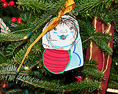 An ornament created my a military child in honor of first lady Michelle Obama is displayed on the Official White House Christmas tree in the Blue Room of the White House in Washington, DC.  The tree features holiday cards created by military children.  Medals, badges, and patches from all of the military branches are displayed on ornaments.  The theme for the White House Christmas 2011 is Shine, Give, Share - celebrating the countless ways we can lift up those around us, put our best self forward in the spirit of the season, spend time with friends and family, celebrate the joy of giving to others, and share our blessings with all.  The theme translates to the holiday décor on several levels. There is the literal translation through the use of shiny elements – star motifs, quartz and metallics like copper, aluminum and mirrored paper. There is also a conceptual connection – we're inviting visitors to give their thanks to members of our military, and have once again invited guest artists to share their talents working with the White House. This year's décor also includes handmade decorations crafted from simple materials – paper, felt, and even recycled cans. These are projects that anyone can do at home using readily available materials that are inexpensive or free..Credit: Ron Sachs / CNP
