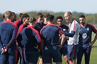 Gregg Berhalter speaks to player during training