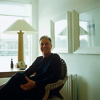 Michael Reeves pictured in cheery mood seated in the study of his London Thames-side apartment
