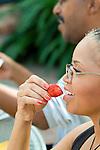 Mature woman holding ripe strawberry
