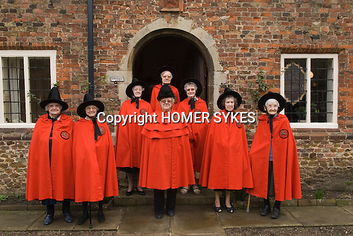 Old Ladies of Castle Rising. The Hospital of the Holy and Undivided Trinity Almshouses, Castle Rising, Norfolk, England 2007. Founders Day. The ladies wear tradiotional red cloaks and pointed black hats. Group of seven plus the warden in centre.