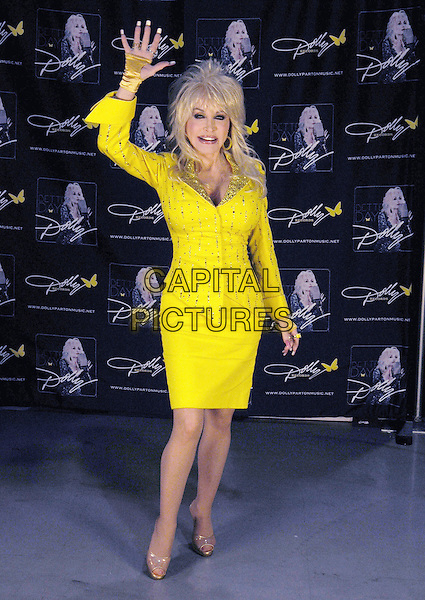 Dolly Parton signs autographs for a limited number of lucky fan winners during the 2011 CMA Music Festival at Fan Fair Exhibit Hall at the Nashvile Convention Center, marking her first autograph session at the event since the mid-'70s. Nashville, Tennessee, USA 11th June 2011.full length yellow dress gold shoes hand arm in air waving skirt jacket beads beaded.CAP/ADM/LF.©Laura Farr/AdMedia/Capital Pictures.