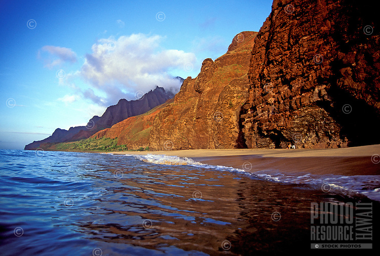 Remote and pristine Kalalau beach on the rugged Na Pali coast, Kauai with wispy clouds on the mountain tops in the distance.