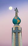 Morning moon at the Monumento al Divino Salvador del Mundo (Monument to the Divine Savior of the World), a monument located on Plaza El Salvador del Mundo (The Savior of the World Plaza) in San Salvador, El Salvador.  It consists of a statue of Jesus Christ standing atop a global sphere of planet earth.