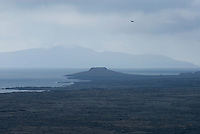 """The distinct shape of Chinese Hat (Sombrero Chino) the little island off the southeastern tip of Santiago as seen from Bartolome. Early visitors to the islands referred to them as """"Las Encandtadas,"""" the Bewitched Islands, because phantom silhouettes seemed to appear and disappear unexplainably on the ocean horizon and volcanic peaks vanished as if by magic in the distant fog.."""