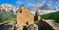 Pictures & images of Gergeti Holy Trinity (Tsminda Sameba) Georgian Orthodox and Apostolic Church and bell tower, 14th century, Gergeti, Khevi province, Georgia (country). At Sunset.