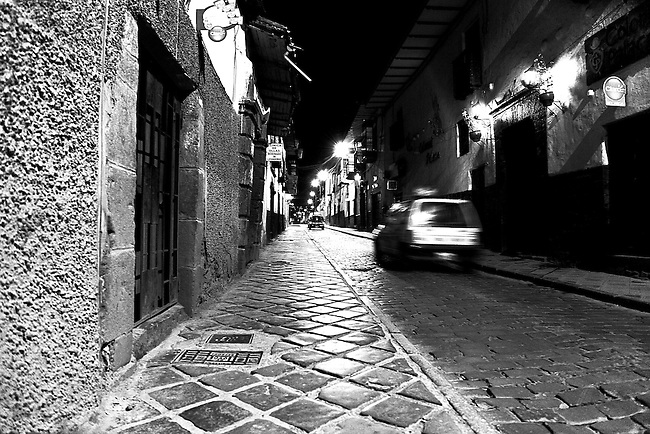 A CAR TRAVELS THE NARROW STREETS OF CUZCO, PERU IN EARLY MORNING
