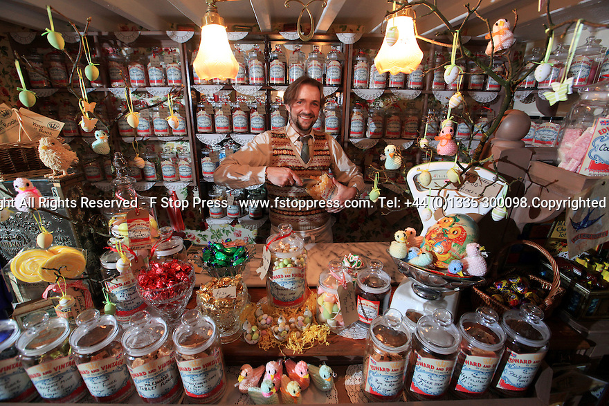 Picture dated 06/03/13 shows David Westcott-Walker (40) behind the counter of his traditional sweet shop, Edward and Vintage, Tissington, Derbyshire.<br /> <br /> Full Copy here:  http://www.fstoppress.com/articles/vintage-sweet-shop/<br /> <br /> The future is looking more than just a little sweet for a vintage sweet shop owner who is in the running to become Britain's Best Vintage Shop of the Year.<br /> <br /> The tiny shop is like a museum exhibiting confectionery from a bygone era. Walking in to Edward and Vintage in the village of Tissington, Derbyshire is like stepping out of a time machine that has traveled back sixty years.<br /> <br /> The shelves are stacked from floor to ceiling with glass jars full of sweets. Each jar has a handwritten label and every name ignites another childhood memory; Pear Drops, Rosy Apples, Lions Wine Gums and Sherbert Lemons are just a few of more than 350 different chunks of nostalgia being sold by the bag.<br /> <br /> It's not only the sweets, fudge and chocolates that are old fashioned. Everything in the shop helps to keep you believing you're in the 1940s - from an old wireless that plays Glen Miller, to the 1920s shop telephone and the antique till that still rings up the prices in old money.<br /> <br /> All Rights Reserved - F Stop Press.  www.fstoppress.com. Tel: +44 (0)1335 300098.
