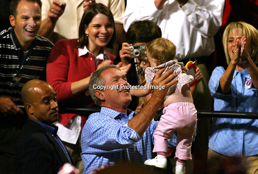 10/14/04,LAS VEGAS,NEVADA --- President George W. Bush holds up a baby at a election campaign rally with GOP governors.  --- CHRIS FARINA  copyright 2004