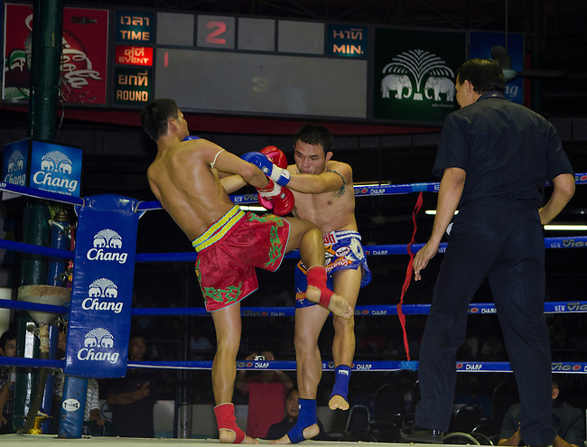 Bangkok, August 30,2011 Lumpini Muay Thai boxing stadium. Mr Singsiam (red trunks) lands a blow with his knee into Mr. Yokpetch as the referee looks on.