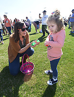 NWA Democrat-Gazette/FLIP PUTTHOFF <br />SCRAMBLE FOR EGGS<br />Chantelle Lookadoo of Springdale helps her daughter, Chloe Lookadoo, 3, find Easter eggs on Saturday March 24 2018 during the Mayor's Easter Egg Hunt in Rogers at Veterans Park. Youngsters 9 and under picked up 11,000 plastic eggs filled with prizes during the Easter egg hunt. Acttivies also included an inflatable playground and an array of games for kids.
