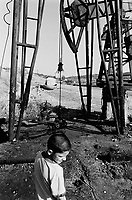 Albania. Province of Fier. Visok. A young boy stands by an oil derrick. An old derelict and destroyed bunker is left upside down on the road. Enver Hoxha (1908-1985) was for 40 years a dictator and a communist leader. He decided after the historic break with Russia in 1961 to protect his country from any invaders by investing in a massive fortification (more than a million bunkers were built over the years till 1985). © 2003 Didier Ruef