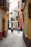 Two men walking down typical old cobbled street in near Hotel Londres, Seville, Spain