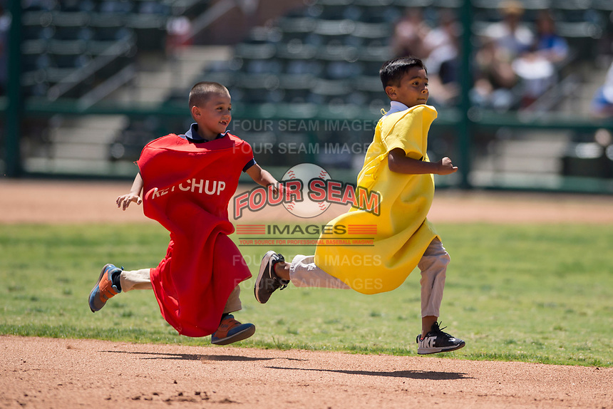 Kids race around the bases dressed as ball park foods and condiments between innings of a California League game between the Visalia Rawhide and Stockton Ports at Visalia Recreation Ballpark on May 9, 2018 in Visalia, California. Stockton defeated Visalia 4-2. (Zachary Lucy/Four Seam Images)