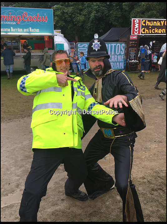 BNPS.co.uk (01202 558833)<br /> Pic: DorsetPolice/BNPS<br /> <br /> Special constable Jason Cox with Elvis at Camp Bestival.<br /> <br /> Hilarious footage of a uniformed police officer 'dad dancing' at a music festival has been captured.<br /> <br /> Cheery special constable Jason Cox couldn't resist strutting his stuff when challenged to a dance off by revelers at Camp Bestival in Dorset. <br /> <br /> SC Cox can be seen throwing his arms into the air and jiggling along to the beat of hip hop hit Hey Ya! by Outkast. <br /> <br /> Dorset Police posted the video to social media, where it has been viewed over 25,000 times.