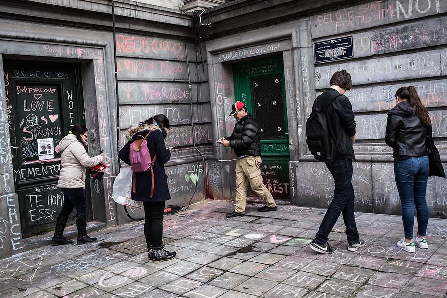 BRUXELLES, Belgique: Des personnes lisent les messages écrits sur les murs de la Bourse en soutien aux victimes des attentats, le 23 mars 2016. 31 personnes sont mortes et 300 ont été blessées dans les attentats commis à Zaventem et dans la station du métro bruxellois Maelbeek, selon le dernier bilan du Centre de crise. Dans le centre de Bruxelles, des centaines de personnes se rassemblent en commemoration aux victimes.