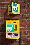 Defibrillator emergency life saving equipment mounted on a wall for public use, Overstrand, Norfolk, England