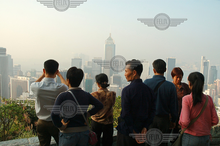 Mainland Chinese tour group (more than half of all visitors come from the mainland), at Stubbs Road Lookout with its view over Hong Kong Island and its skyscrapers, with Central Plaza in Wan Chai at centre.