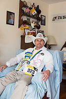 Carlos Arredondo, 57, is seen in his home in Roslindale, Boston, Massachusetts, USA, on Sat., March 31, 2018. Arredondo is well known as the &quot;man in the cowboy hat&quot; who helped out in the aftermath of the Boston Marathon Bombing in 2013. Carlos is wearing a jacket that he has used to create a t-shirt design for when he runs the Boston Marathon later this year. Though he has run the race unofficially previously, this will be the first time he runs it &quot;legally,&quot; he says.<br /> <br /> Carlos' son Brian Arredondo, who can be seen in the photo on the wall above Carlos, died by suicide in 2011 after a battle with depression following the 2004 death of Arrendondo's other son  Marine Lance Corporal Alexander Scott Arredondo, who was killed while serving in Iraq.